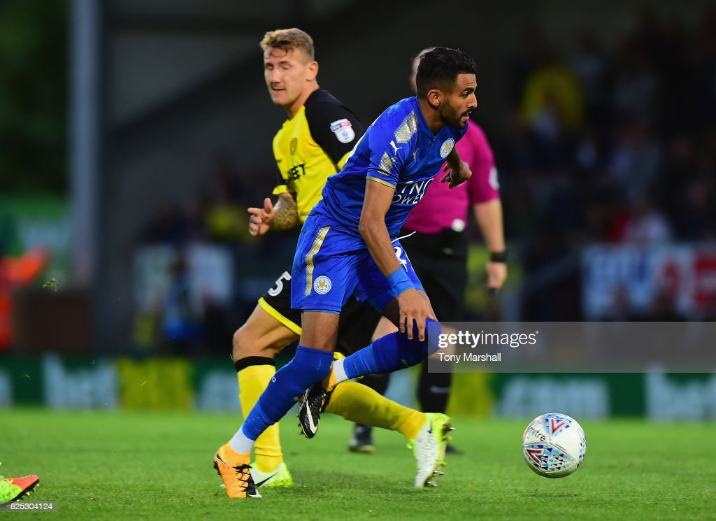 Riyad Mahrez of Leicester City gets past a challenge from Kyle McFadzean of Burton Albion during the Pre-Season Friendly match between Burton Albion v Leicester City at Pirelli Stadium on August 1, 2017 in Burton-upon-Trent, England.