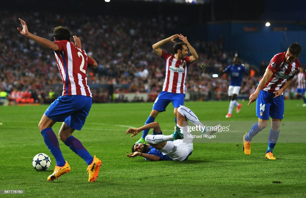 Riyad Mahrez of Leicester City goes to ground after a challenge by Gabi (R) of Atletico Madrid in the penalty area during the UEFA Champions League Quarter Final first leg match between Club Atletico de Madrid and Leicester City at Vicente Calderon Stadium on April 12, 2017 in Madrid, Spain.