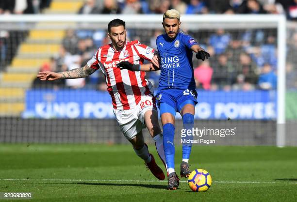 Riyad Mahrez of Leicester City is challenged by Geoff Cameron of Stoke City during the Premier League match between Leicester City and Stoke City at...