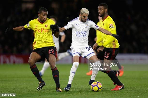 Riyad Mahrez of Leicester City is challenged by Marvin Zeegelaar and Molla Wague of Watford during the Premier League match between Watford and...