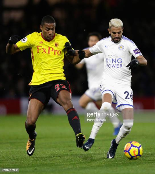 Riyad Mahrez of Leicester City is challenged by Marvin Zeegelaar of Watford during the Premier League match between Watford and Leicester City at...