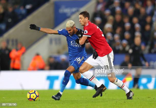 Riyad Mahrez of Leicester City is challenged by Nemanja Matic of Manchester United during the Premier League match between Leicester City and...