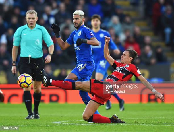Riyad Mahrez of Leicester City is tackled by Chris Lowe of Huddersfield Town during the Premier League match between Leicester City and Huddersfield...
