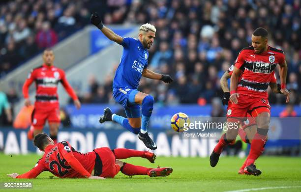 Riyad Mahrez of Leicester City is tackled by Christopher Schindler of Huddersfield Town during the Premier League match between Leicester City and...
