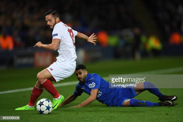 Riyad Mahrez of Leicester City is tackled by Pablo Sarabia of Sevilla during the UEFA Champions League Round of 16 second leg match between Leicester...