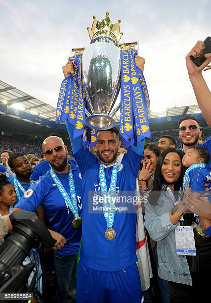 Riyad Mahrez of Leicester City lifts the Premier League Trophy as players celebrate the season champions after the Barclays Premier League match...