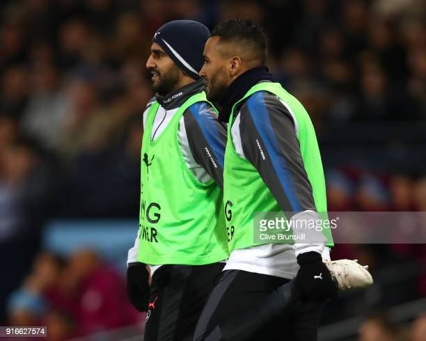 Riyad Mahrez of Leicester City speaks to Danny Simpson of Leiceter City as they warm up during the Premier League match between Manchester City and...