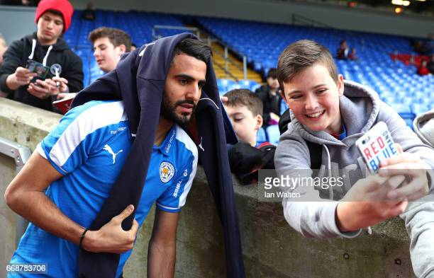 Riyad Mahrez of Leicester City takes a selfie photograph with a fan prior to the Premier League match between Crystal Palace and Leicester City at...