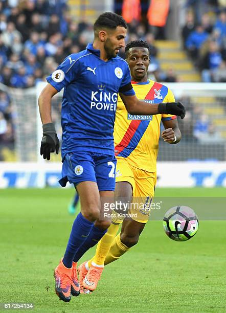 Riyad Mahrez of Leicester City takes the ball past Wilfried Zaha of Crystal Palace during the Premier League match between Leicester City and Crystal...