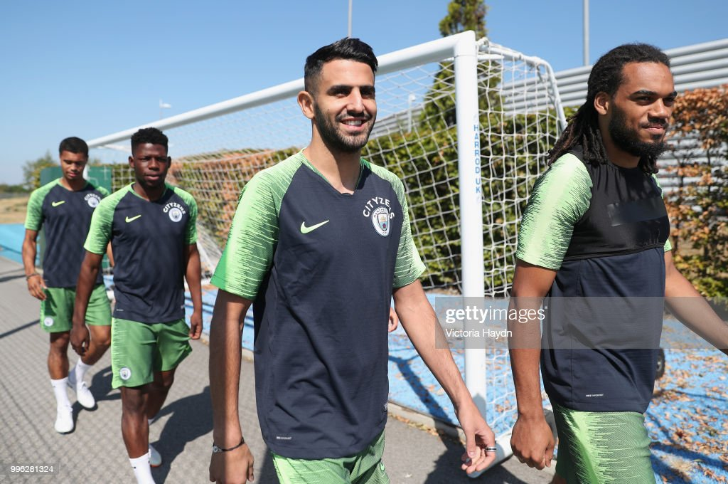 Riyad Mahrez (2ndR) of Manchester City arrives with team mates to take part in his first training session at Manchester City Football Academy on July 11, 2018 in Manchester, England.