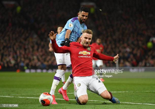 Riyad Mahrez of Manchester City battles for possession with Luke Shaw of Manchester United during the Premier League match between Manchester United...