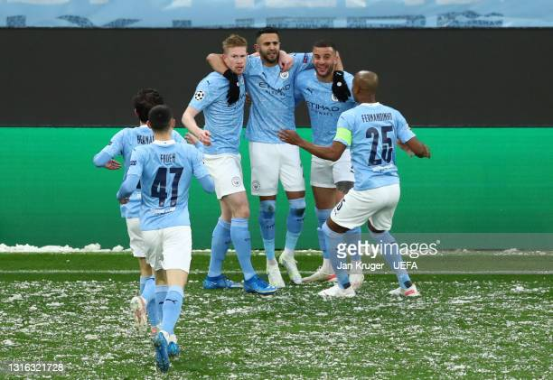 Riyad Mahrez of Manchester City celebrates with Kevin De Bruyne, Kyle Walker and Fernandinho after scoring his team's first goal during the UEFA...