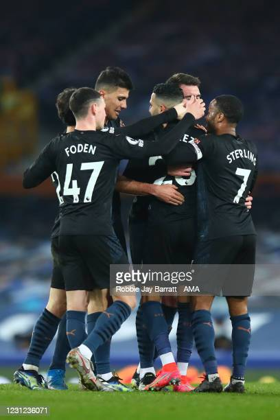 Riyad Mahrez of Manchester City celebrates with team mates after scoring a goal to make it 1-2 during the Premier League match between Everton and...