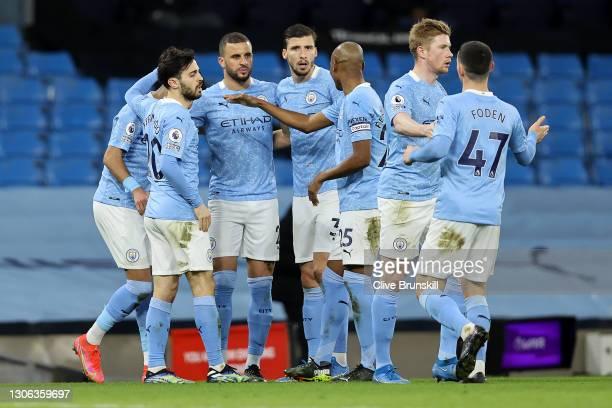 Riyad Mahrez of Manchester City celebrates with team mates Bernardo Silva, Kyle Walker, Ruben Dias, Fernandinho, Kevin De Bruyne and Phil Foden after...