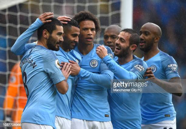 Riyad Mahrez of Manchester City celebrates with teammates after scoring his team's fourth goal during the Premier League match between Cardiff City...