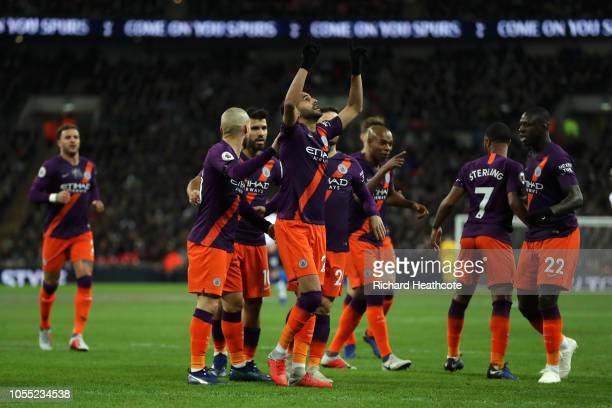Riyad Mahrez of Manchester City celebrates with teammates after scoring his team's first goal during the Premier League match between Tottenham...
