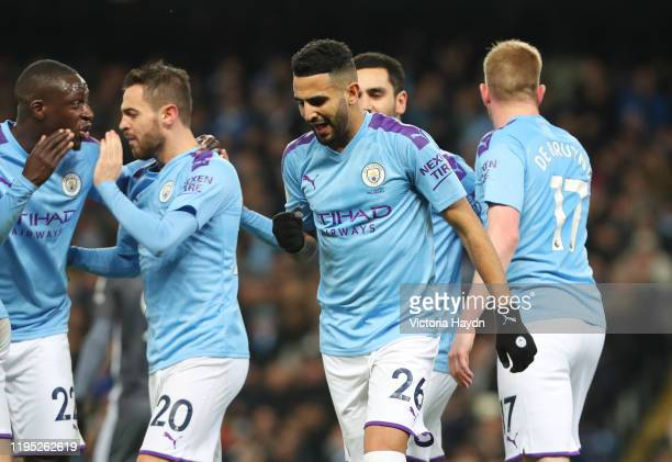 Riyad Mahrez of Manchester City celebrates with teammates after scoring his team's first goal during the Premier League match between Manchester City...