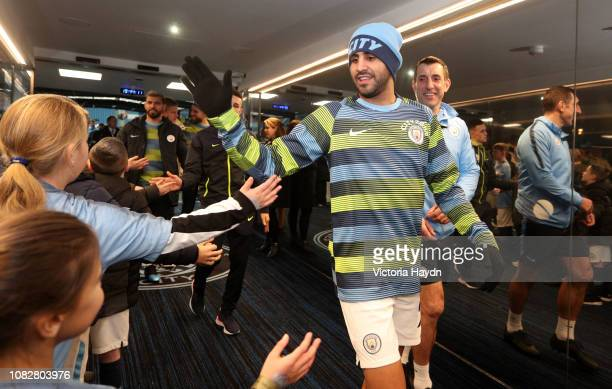 Riyad Mahrez of Manchester City high fives the mascots in the tunnel prior to the Premier League match between Manchester City and Wolverhampton...