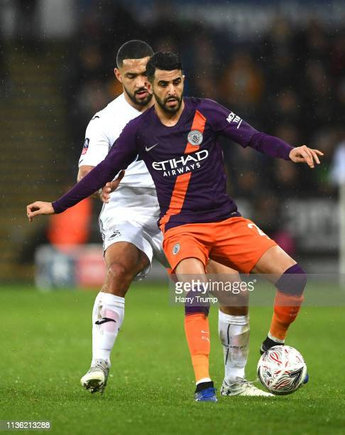Riyad Mahrez of Manchester City is challenged by Cameron CarterVickers of Swansea City during the FA Cup Quarter Final match between Swansea City and...