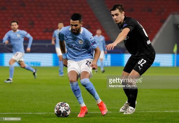 Riyad Mahrez of Manchester City is challenged by Florian Neuhaus of Borussia Mönchengladbach during the UEFA Champions League Round of 16 match...
