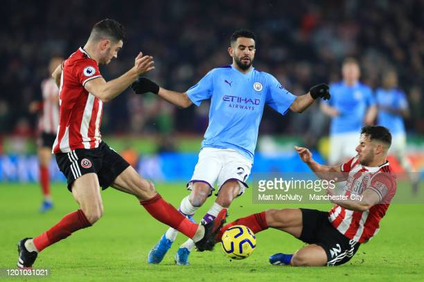 Riyad Mahrez of Manchester City is challenged by John Egan and George Baldock of Sheffield United during the Premier League match between Sheffield...