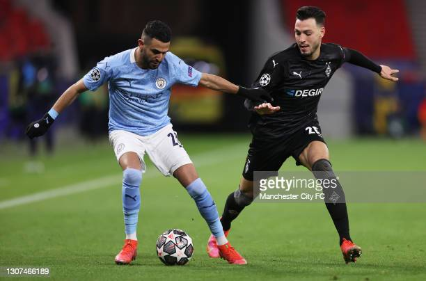 Riyad Mahrez of Manchester City is closed down by Ramy Bensebaini of Borussia Moenchengladbach during the UEFA Champions League Round of 16 match...