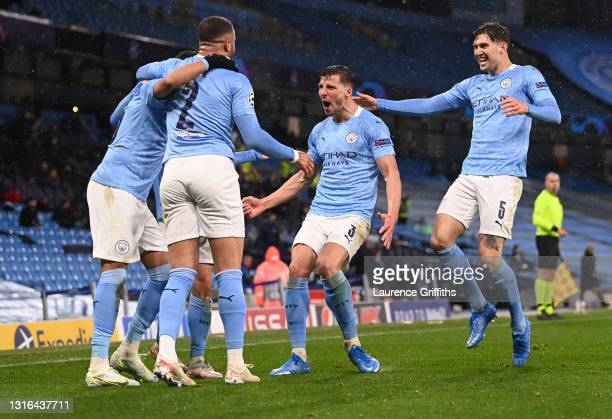 Riyad Mahrez of Manchester City is congratulated on scoring his team's second goal by Ruben Dias and John Stones during the UEFA Champions League...