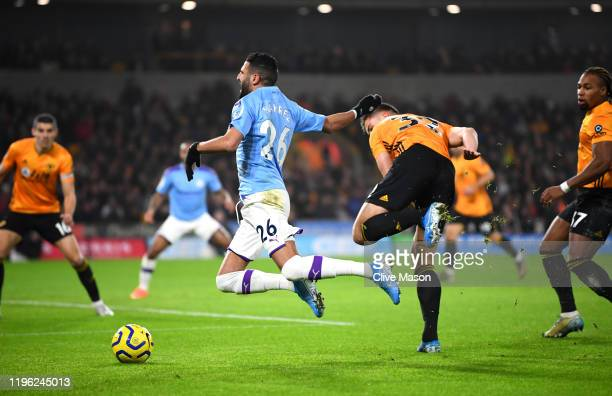 Riyad Mahrez of Manchester City is tripped by Leander Dendoncker of Wolverhampton Wanderers leading to the first Manchester City penalty during the...