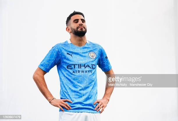 Riyad Mahrez of Manchester City poses wearing the 2020/21 Puma home jersey at the City Football Academy on August 03, 2020 in Manchester, England.