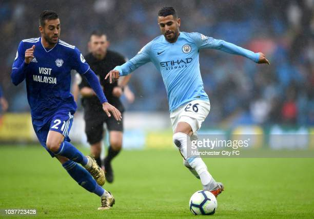 Riyad Mahrez of Manchester City runs with the ball under pressure from Victor Camarasa of Cardiff City during the Premier League match between...