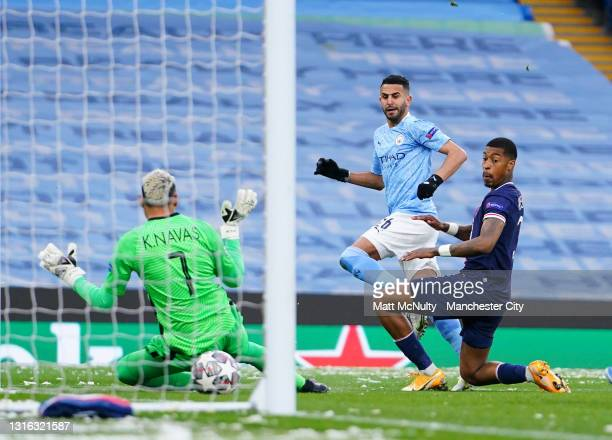 Riyad Mahrez of Manchester City scores his team's first goal while under pressure from Presnel Kimpembe of Paris Saint-Germain during the UEFA...