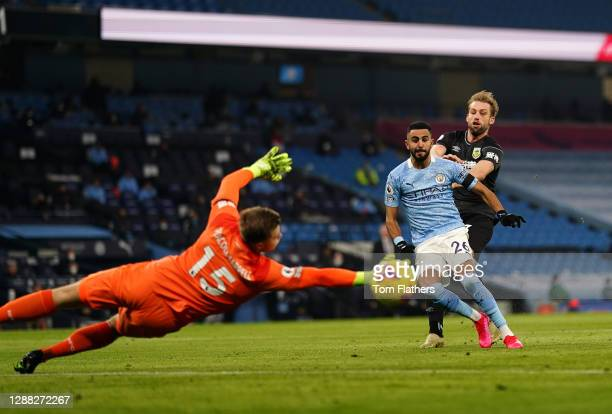 Riyad Mahrez of Manchester City scores their team's first goal past Bailey Peacock-Farrell of Burnley during the Premier League match between...
