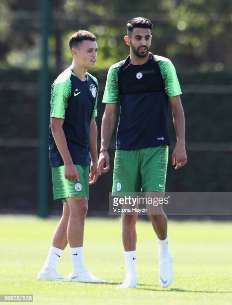 Riyad Mahrez of Manchester City talks with Phil Foden as he takes part in his first training session at Manchester City Football Academy on July 11...