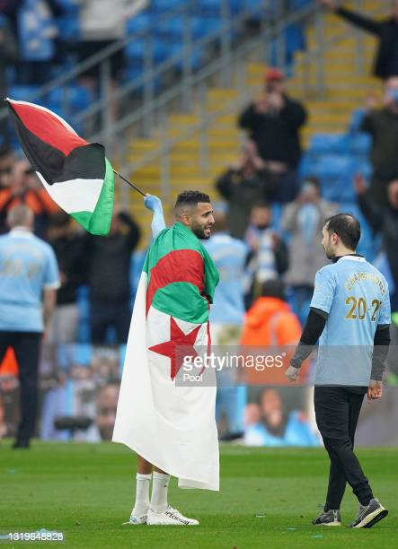 Riyad Mahrez of Manchester City wears the flag of Algeria, as he carries the flag of Palestine after Manchester City are presented with the Premier...