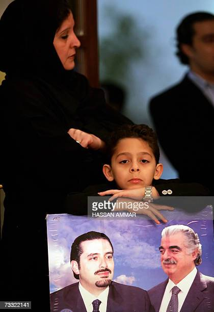 A boy poses with a portrait of late prime minister Rafiq Hariri and his son Saad during a ceremony to mark Hariri's death at the Lebanese embassy in...