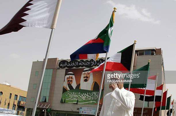 A man passes in front a huge portrait of Saudi King Abdullah bin Abdul Aziz and Saudi Crown Prince Sultan bin Abdulaziz alSaud as Arab flags wave in...