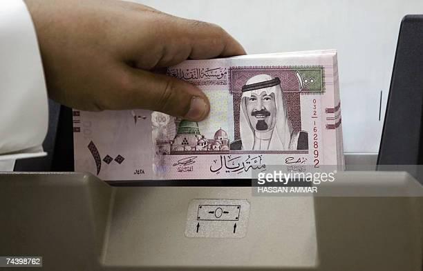 A Saudi banker counts new one hundred riyals bearing the portrait of Saudi King Abdullah bin Abdul Aziz alSaud at a bank in Riyadh 05 June 2007 The...