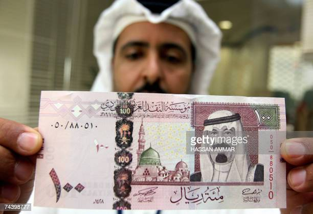 A Saudi banker displays the new one hundred riyal banknote bearing the portrait of Saudi King Abdullah bin Abdul Aziz alSaud at a bank in Riyadh 05...