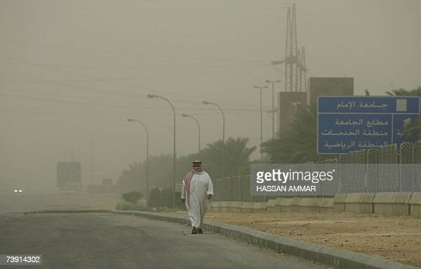 A Saudi man walks in the street as he covers his face with a Saudi traditional head dress cover during a massive sandstorm in Riyadh 18 April 2007...