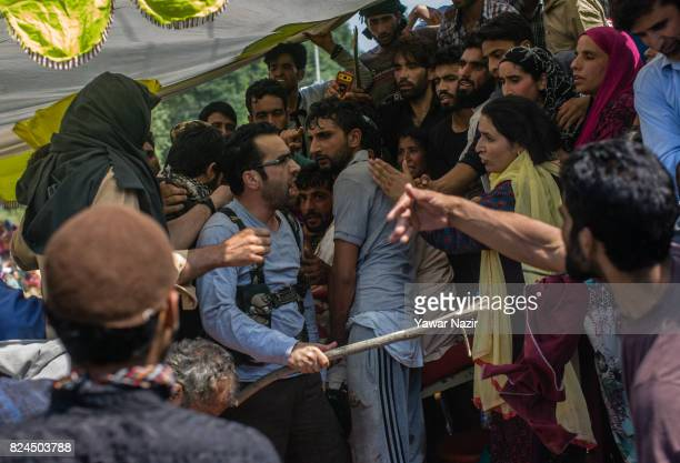 Riyaz Naikoo a top commander of Kashmir's largest rebel group Hizbul Mujahideen holds back Kashmiri Muslim sympathizers during the funeral of Shariq...