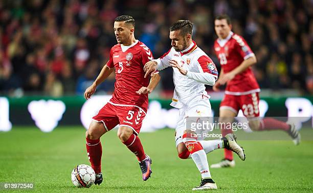 Riza Durmisi of Denmark and Marko Vesovic of Montenegro compete for the ball during the FIFA World Cup 2018 european qualifier match between Denmark...