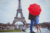 Rmantic couple in Paris kissing near Eiffel towe.