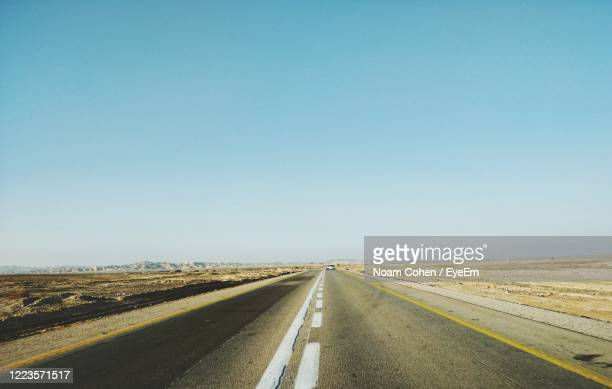 road against clear blue sky - noam cohen stock pictures, royalty-free photos & images