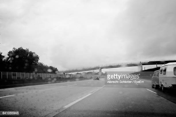 road against cloudy sky seen through windshield - albrecht schlotter stock photos and pictures