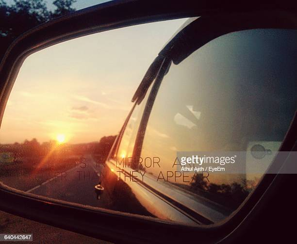 Road Against Sky Reflecting On Side-View Mirror Of Car During Sunset