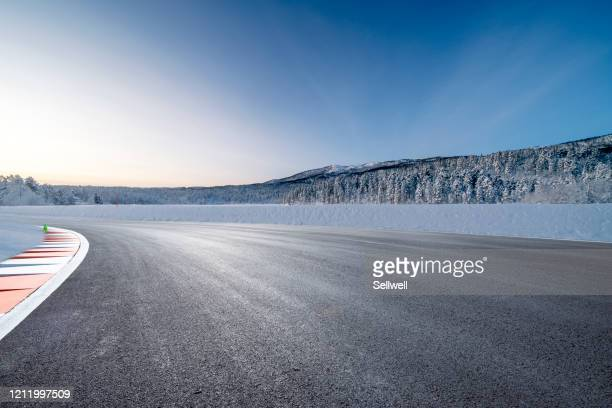 road against snowcapped mountain - sports track stock pictures, royalty-free photos & images