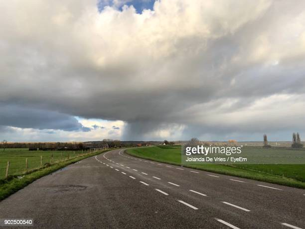 road against storm clouds over landscape - amersfoort netherlands stock photos and pictures