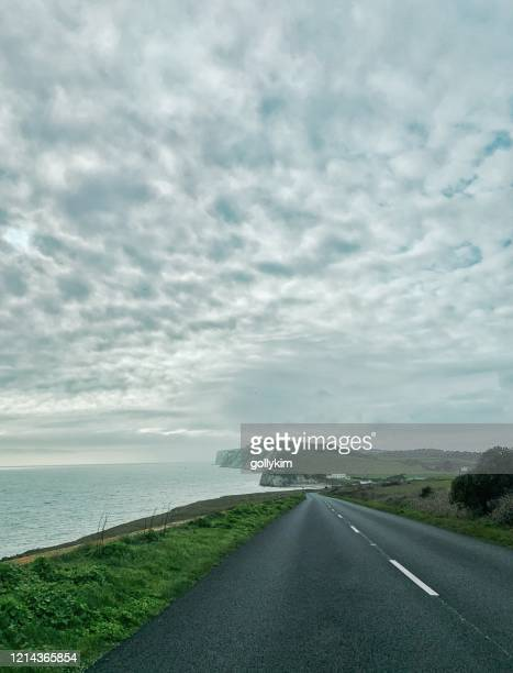 road along freshwater bay with cirrocumulus cloud, isle of wight, england - freshwater bay isle of wight stock pictures, royalty-free photos & images