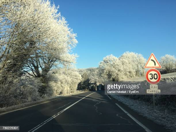 Road Amidst Bare Trees Against Clear Sky