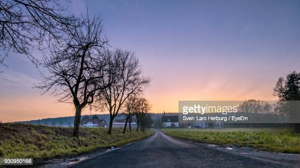 Road Amidst Bare Trees Against Sky During Sunset